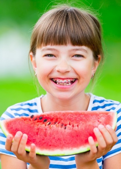 Girl with braces eating watermelon